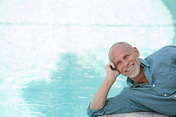 handsome man leaning on his elbow and smiling by a swimming pool