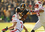 November 02 2013: Iowa Hawkeyes running back Damon Bullock (5) prepares to be hit by Wisconsin Badgers safety Michael Caputo (7) and Wisconsin Badgers linebacker Marcus Trotter (59) during the first half of the NCAA football game between the Wisconsin Badgers and the Iowa Hawkeyes at Kinnick Stadium in Iowa City, Iowa on November 2, 2013. Wisconsin defeated Iowa 28-9.