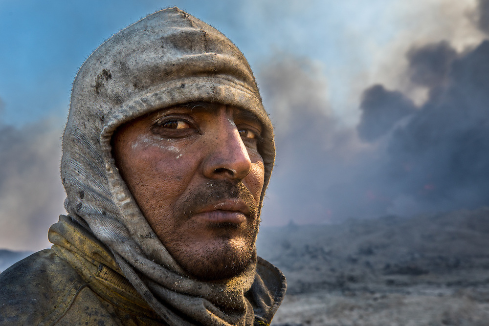 A Firefighter from Kirkuk, Iraq pauses to rest. The pride these men have in their work shows in their faces. They claim that they don't do it for the money, but for their country. Qayyara, Iraq. Nov. 23, 2016. (Photo by Gabriel Romero ©2016)