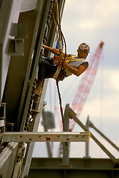 Workman operates a powered torque driver while suspended from a harness.