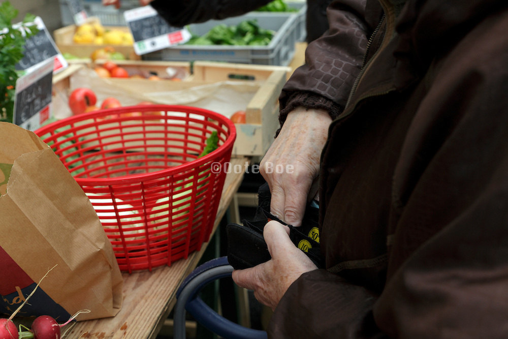 senior woman getting small change at an outdoor vegetable stand