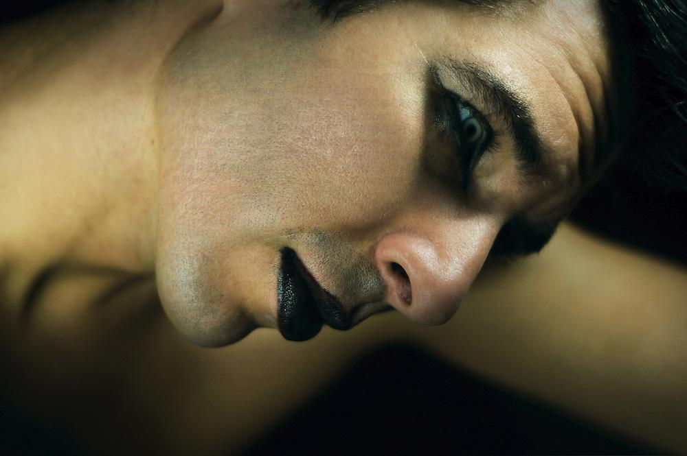 Close up of a young man's face wearing makeup