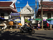 29 NOVEMBER 2015 - BANGKOK, THAILAND:   Traffic goes by the gate to Wat Maharat on Maharat Road on the last day amulet vendors (under the large umbrellas) were allowed to do business on the street. Hundreds of vendors used to sell amulets and Buddhist religious paraphernalia to people in the Amulet Market, a popular tourist attraction along Maharat Road north of the Grand Palace near Wat Maharat in Bangkok. Bangkok municipal officials announced that they are closing the market and forcing vendors to relocate to an area about one hour outside of Bangkok. The closing of the amulet market is the latest in a series of municipal efforts to close and evict street vendors and markets from areas that have potential for redevelopment. The street vendors were evicted from the area on Sunday, Nov. 29.      PHOTO BY JACK KURTZ