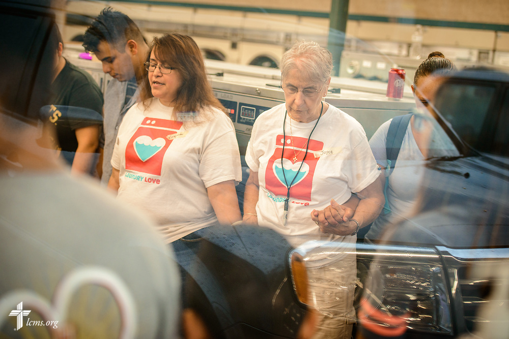 "Inside, Joyce Bauer (center, right) joins other volunteers from St. Paul Lutheran Church, San Antonio, Texas, as they pray during Laundry Love on Wednesday, Aug. 2, 2017, at the E-Z Wash laundromat in San Antonio. The monthly ministry event is supported by a grant through the ""Stand With Your Community"" program, which was made possible by a partnership between the LCMS, Thrivent Financial and Lutheran Church Extension Fund. LCMS Communications/Erik M. Lunsford"