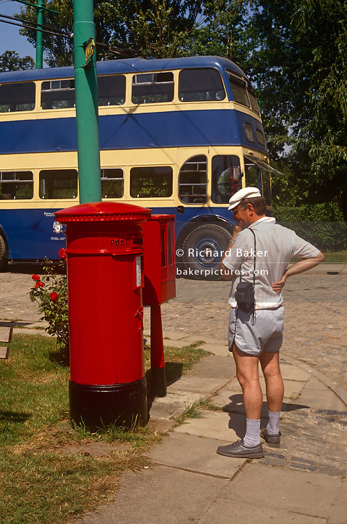 A visitor pauses to read the writing on a Royal Mail postal box while walking round the East Anglia Transport Museum, Lowestoft, Suffolk, England. A Routemaster double-decker bus in a local bus company colours sits in the sunshine - well-maintained and pristine in the sunshine.