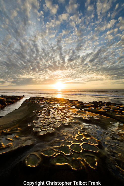 I took this bizarre photo of tide pools and clouds because the odd clouds matched the little round weird tide pools.  The setting sun lights up the odd sandstone patterns.