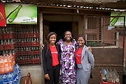 Peace (right) and Ifeoma (left) from Youth for Technology pictured here with Ojiugi Ogbuji.<br /> <br /> Ojiugi started her business in 2000, beginning with door to door sales of baby items. <br /> <br /> She later expanded into the unit next door and started selling soft drinks and water too. <br /> <br /> She attended the Youth for Technology business training first and then heard about the business advice SMS service. <br /> <br /> The main thing she learnt from the training was about the importance of eye-catching displays to attract people into the shop and also the value of loans.