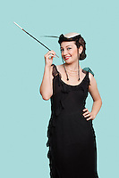 Portrait of happy young woman in black dress holding old-fashioned cigarette holder against blue background