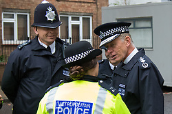 London, August 31st 2015. Met Police Commissioner Sir Bernard Hogan-Howe chats with police officers as revellers ignore the inclement weather to enjoy day two of the Notting Hill Carnival.