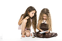 caucasian little girls playing game console isolated studio on white background