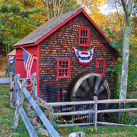 The Medfield Kingsbury Grist Mill in Massachusetts on a beautiful autumn picture perfect day. This is a more intimate view of this historic watermill. The warm light painted the fall foliage tree canopy in gorgeous colors which stand in nice contrast with the historic landmark rotating waterwheel.<br />