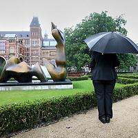 Nederland, Amsterdam , 20 juni 2013.<br /> Her Rijksmuseum laat in zijn vernieuwde tuinen een overzicht zien van 12 sculpturen van Henry Moore. rode draad in het oeuvre van Moore vormen zijn iconische liggende vrouwenfiguren, waarvan verschillende versies zich uitstrekken op het gras van het Rijksmuseum.<br /> De sculpturen van Henry Moore vinden in het stedelijke groen, tussen de vaste klassieke beeldcollectie van de Rijksmuseumtuinen en het neogotische museumgebouw van architect Cuypers een prachtig decor.<br /> Op de foto een beveiliger bij de sculptuur Two piece reclining figure cut uit 1979-81. Rechts sculptuur Reclining figure Arch Leg uit 1969-70<br /> Foto:Jean-Pierre Jans