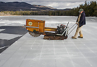 Carl Hansen operates the ice cutter with precision during day one of the annual three day ice harvest with the Rockywold-Deephaven Camp crew on Wednesday.  (Karen Bobotas/for the Laconia Daily Sun)