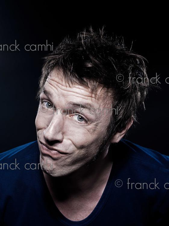 studio portrait on black background of a funny expressive caucasian man puckering suspicious