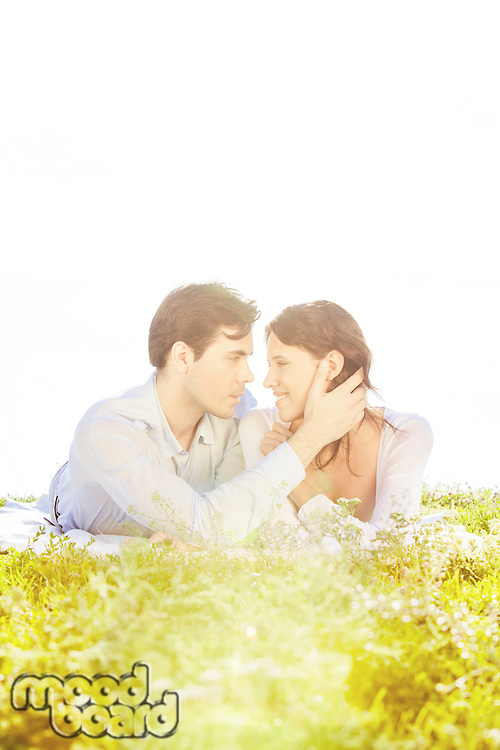 Affectionate man touching woman while looking at her on grass against clear sky