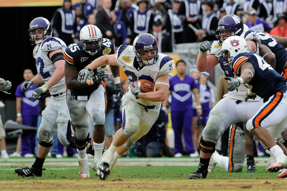January 1, 2010: Running back Jacob Schmidt of the Northwestern Wildcats rushes upfield during the NCAA football game between the Northwestern Wildcats and the Auburn Tigers in the Outback Bowl. The Tigers defeated the Wildcats 38-35 in overtime.