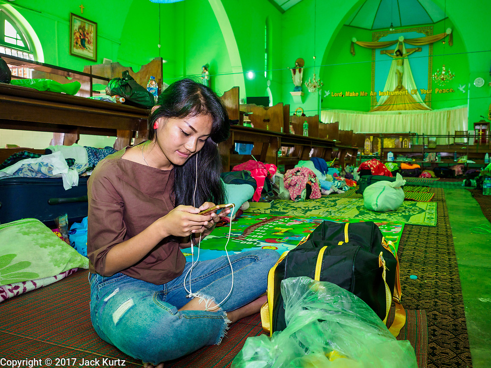 28 NOVEMBER 2017 - YANGON, MYANMAR: A woman from upcountry Myanmar who said she is going to the papal mass Wednesday, checks her smart phone in the sanctuary at St. Francis of Assisi Church in Yangon. About 1,500 people are camping at the church before the papal mass at Kyaikkasan Sports Ground, about three kilometers from the church.    PHOTO BY JACK KURTZ