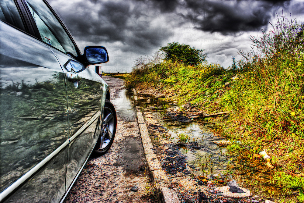 Shiny reflections of some dumped roadside rubbish in the side of a mazda 6 with ominous moody stormy skies as a backdrop