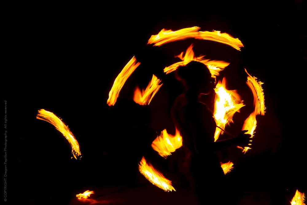 female fire dancer swirling umbrella of flames during a fire dancing ceremony at Aquana Beach Resort, Eratap, Efate Vanuatu in the South Pacific