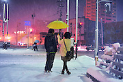 A Japanese couple standing in the snow sheltered from the cold and snow by an umbrella and their warm love.