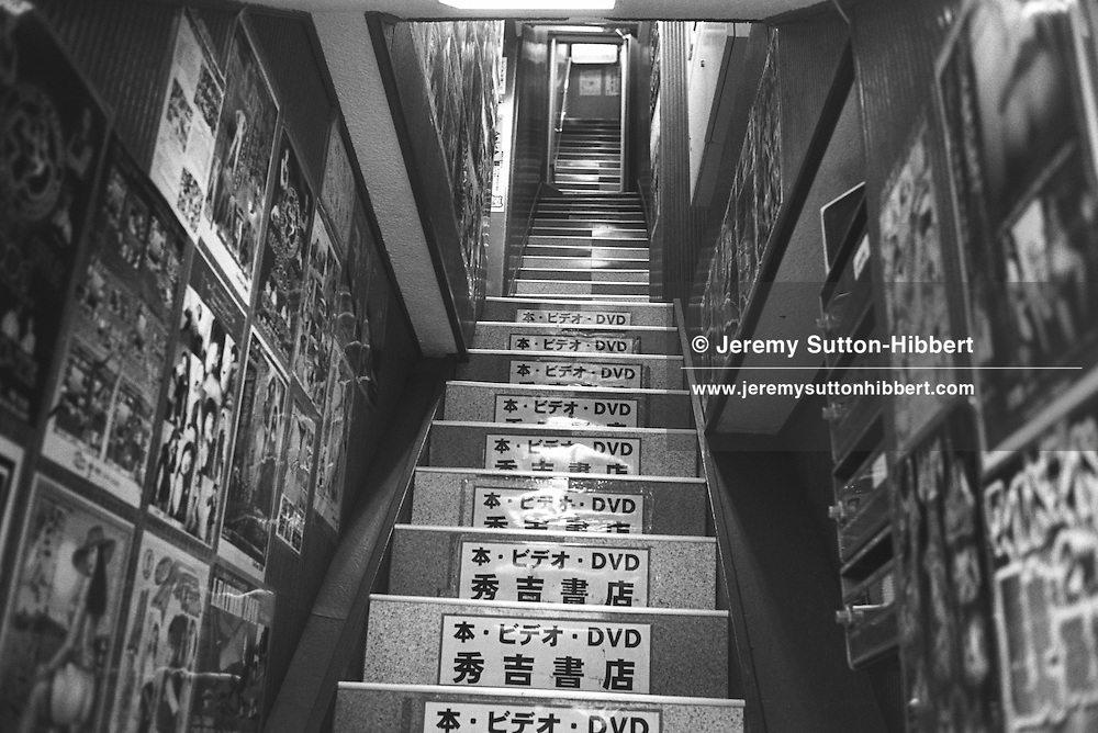 Stairs leading up to a shop selling DVD's, mainly of a pornographic nature. Tokyo, Japan.