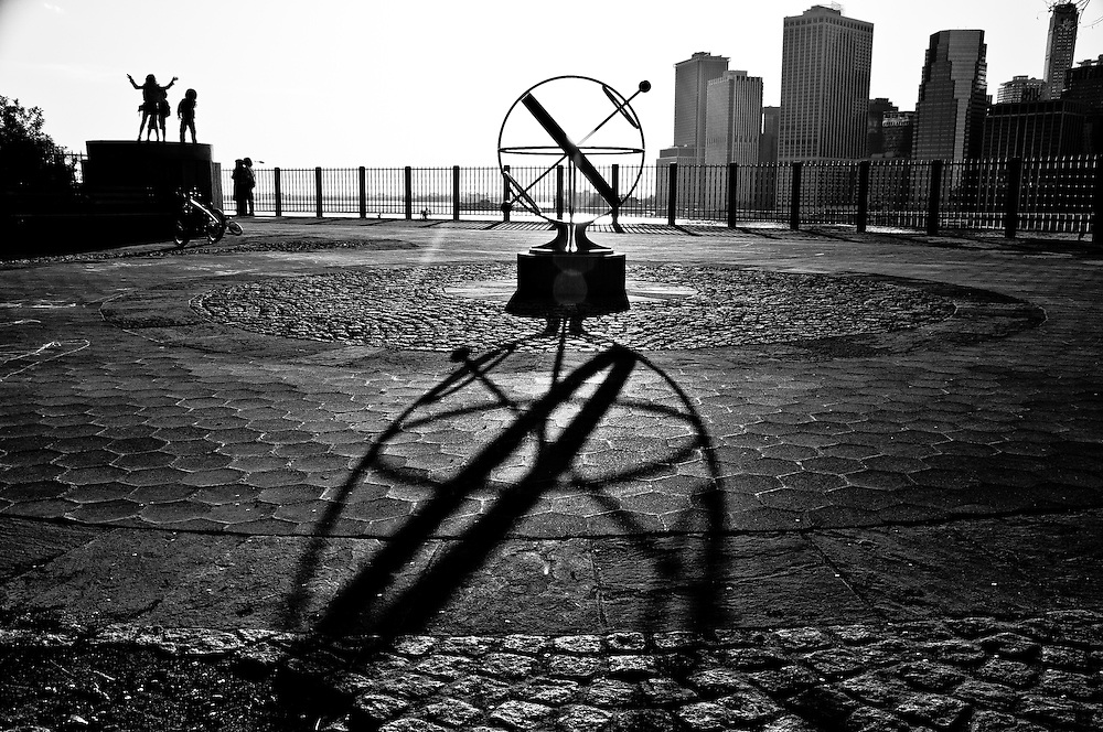 The shadow of globe statue on the Brooklyn heights Promenade, with children playing and the Wall Street skyline in the background, New york.