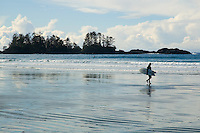 surfer walks Chesterman Beach, Tofino, BC