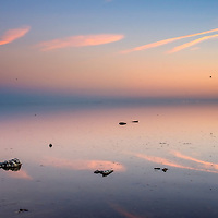 Peaceful lakeside scene with blue and pink reflections in the water