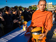 "20 JANUARY 2017 - BANGKOK, THAILAND: A Buddhist monk finishes his alms collecting during a ""tak bat"" (alms giving ceremony) on the plaza in front of Bangkok's City Hall. Hundreds of municipal workers and civil servants made merit by praying and presenting alms to 89 Buddhist monks Friday to mark 100 days of mourning since the death of revered Bhumibol Adulyadej, the Late King of Thailand. The significance of 89 monks is that the King, who died on October 13, 2016, was a few weeks short of his 89th birthday.        PHOTO BY JACK KURTZ"
