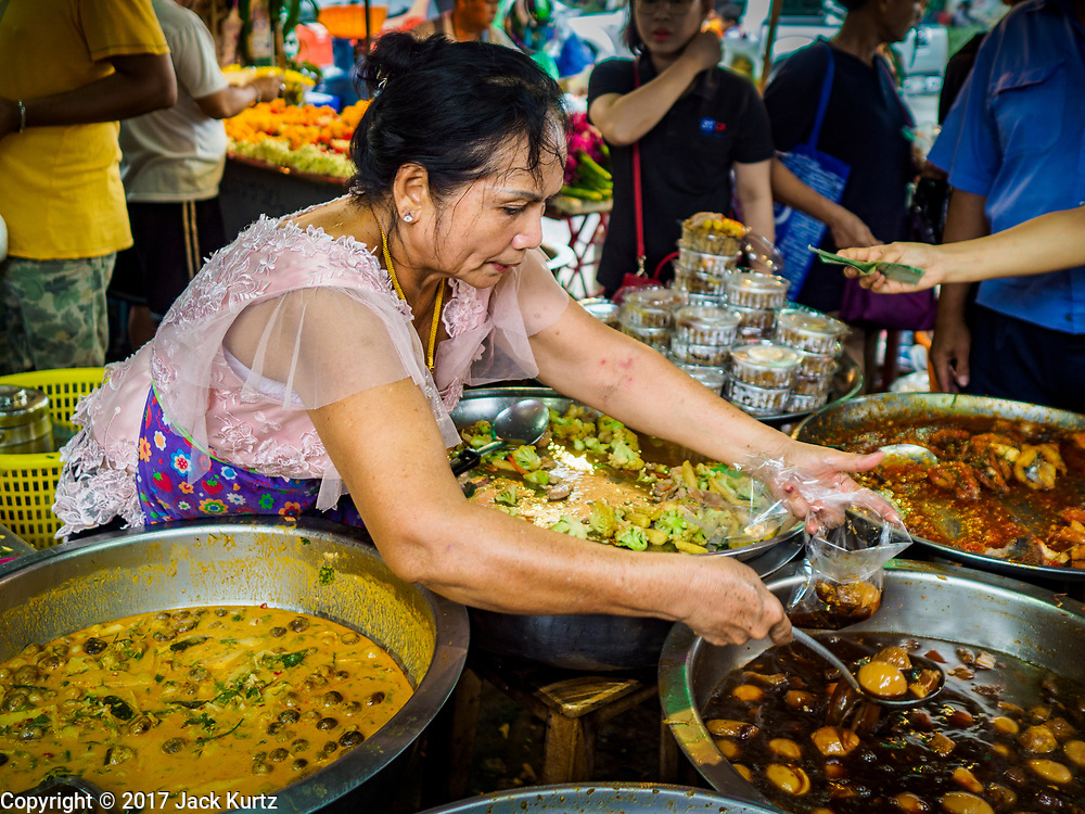 08 JUNE 2017 - BANGKOK, THAILAND: A food vendor packages a to-go order for customer in Khlong Toey Market, Bangkok's main fresh market. Thai consumer confidence dropped for the first time in six months in May following a pair of bombings in Bangkok, low commodity prices paid to farmers and a sharp rise in the value of the Thai Baht versus the US Dollar and the EU Euro. The Baht is surging because of political uncertainty, related to Donald Trump, in the US and Europe. The Baht's rise is being blamed for a drop in Thai exports. This week the Baht has been trading at around 33.90 Baht to $1US, it's highest point in two years.      PHOTO BY JACK KURTZ