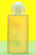 frosted glass perfume bottle object on yellow green background