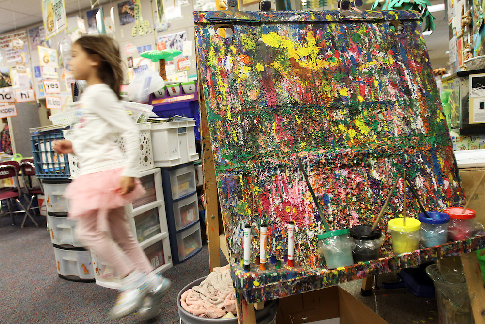 This easel is covered in 18 years worth of fingerpaint. Diane Bonica, longtime kindergarten teacher at Deer Creek Elementary School in Tigard, works with this year's crop of children on Wednesday, May 23, 2012.