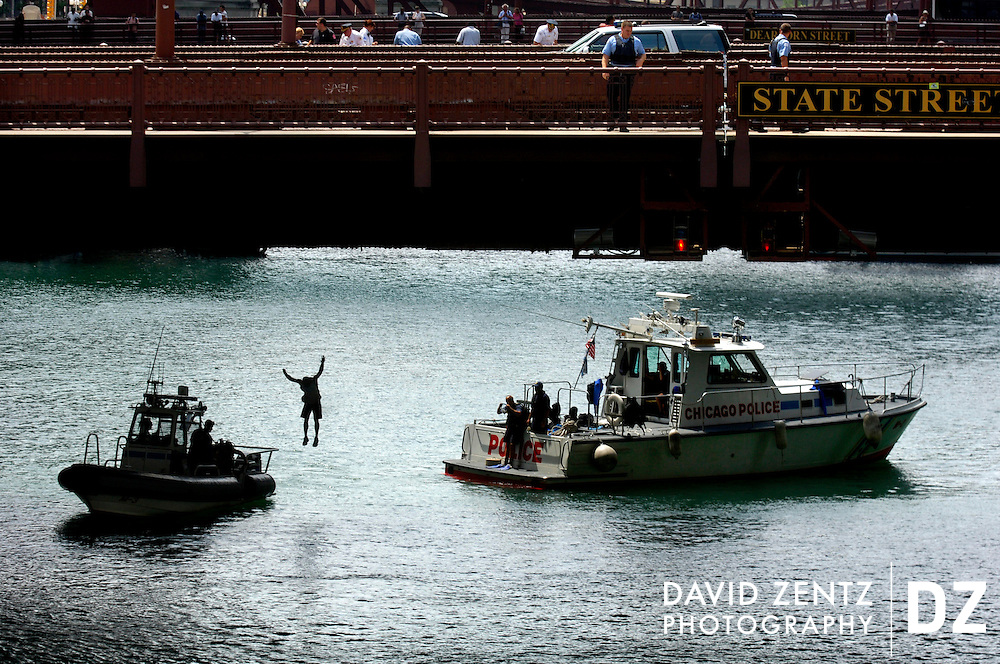 After threatening suicide, an unidentified man drops into the Chicago River from the State Street Bridge in downtown Chicago, Ill.