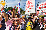 22 DECEMBER 2013 - BANGKOK, THAILAND:  An anti-government protestors chant as they march past roadblock blocking the road to the home of Yingluck Shinawatra. Hundreds of thousands of Thais gathered in Bangkok Sunday in a series of protests against the caretaker government of Yingluck Shinawatra. The protests are a continuation of protests that started in early November and have caused the dissolution of the Pheu Thai led government of Yingluck Shinawatra. Protestors congregated at home of Yingluck and launched a series of motorcades that effectively gridlocked the city. Yingluck was not home when protestors picketed her home.    PHOTO BY JACK KURTZ