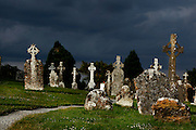 Low angle view of gravestones near the Temple Hurpan and Dowling or Doolin, Clonmacnoise, County Offaly, Ireland, against a dramatic evening sky. Clonmacnoise was founded by St Ciaran, with the help of Diarmait Ui Cerbaill, Ireland's first Christian King. The site presents the largest collection of Early Christian graveslabs in Western Europe. Picture by Manuel Cohen