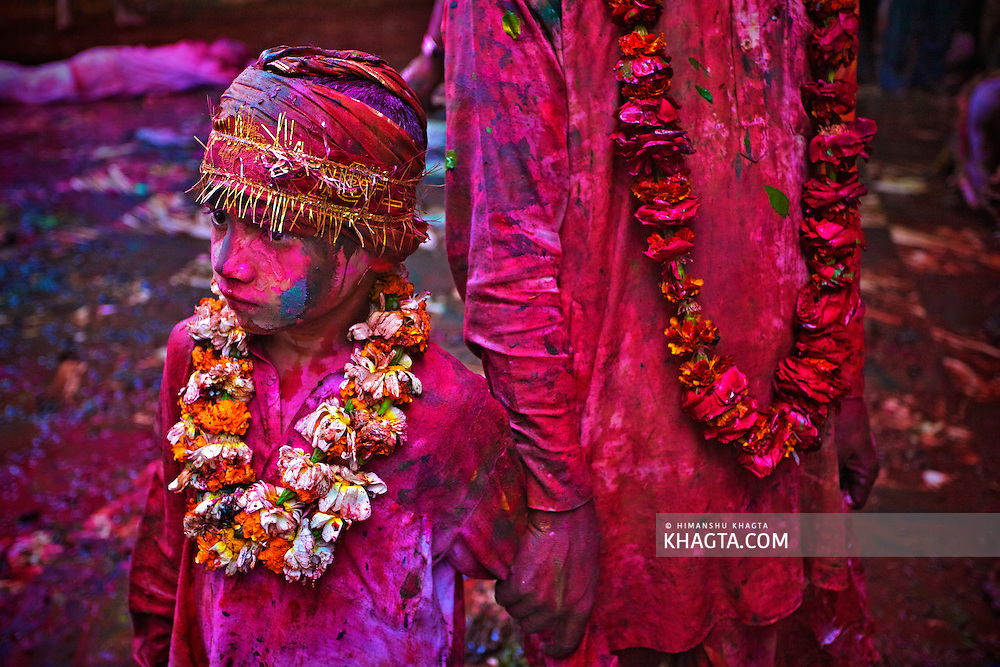 A father holds his child smeared with colors at Nand Gaon village after celebrating, 'The festival of Holi', in the village.