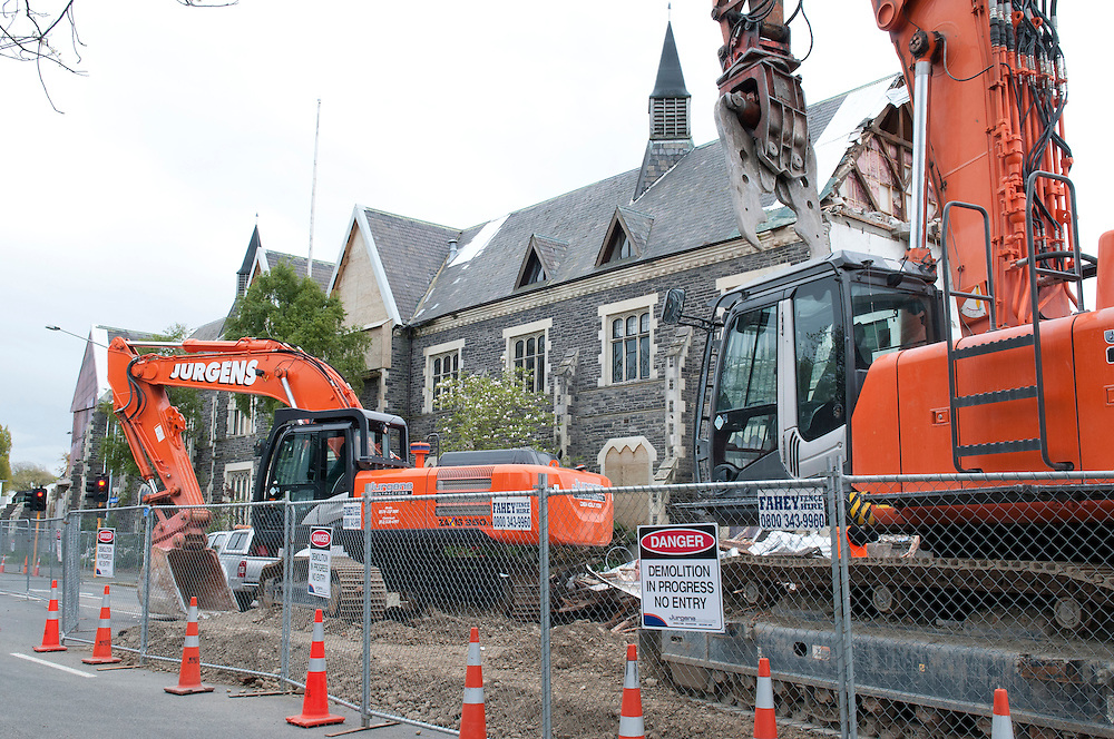 Demolition work starts on Cranmer Courts as a protest against the demolition of the earthquake damaged heritage buildings is held nearby, Cranmer Square,  Christchurch, New Zealand,  Thursday 4 October, 2012. Credit: SNPA /  David Alexander.