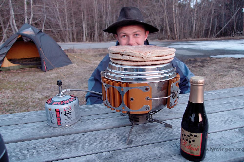 Man with heating water on Omni fuel burner, tent in the background - Mann varmer vann og lefser på en omnifuel brenner, telt i bakgrunnen