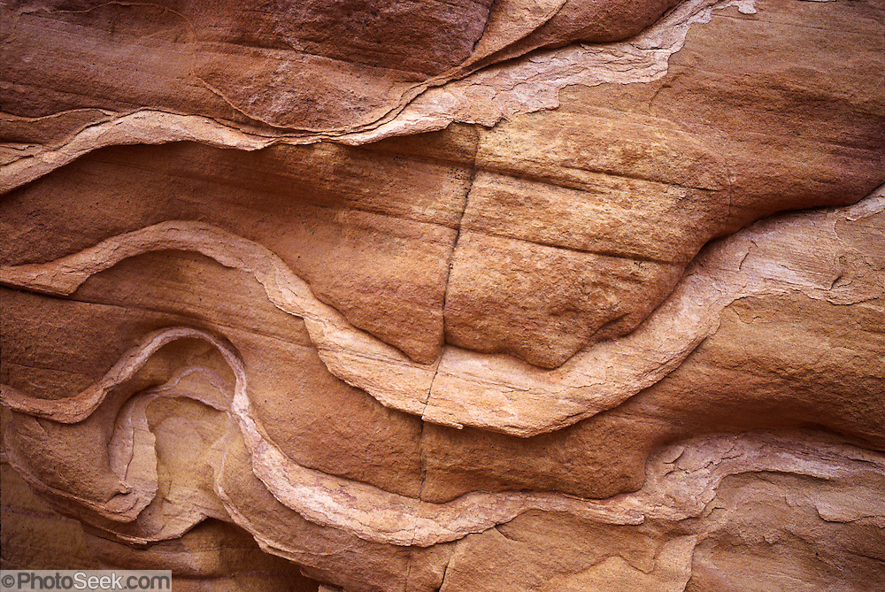 Wavy sandstone pattern by Carol Dempsey, Valley of Fire State Park, Nevada, USA. Starting more than 150 million years ago, great shifting sand dunes during the age of dinosaurs were compressed, uplifting, faulted, and eroded to form the park's fiery red sandstone formations. The park adjoins Lake Mead National Recreation Area at the Virgin River confluence, at an elevation of 2000 to 2600 feet (610-790 m), 50 miles (80 km) northeast of Las Vegas, USA. Park entry from Interstate 15 passes through the Moapa Indian Reservation.
