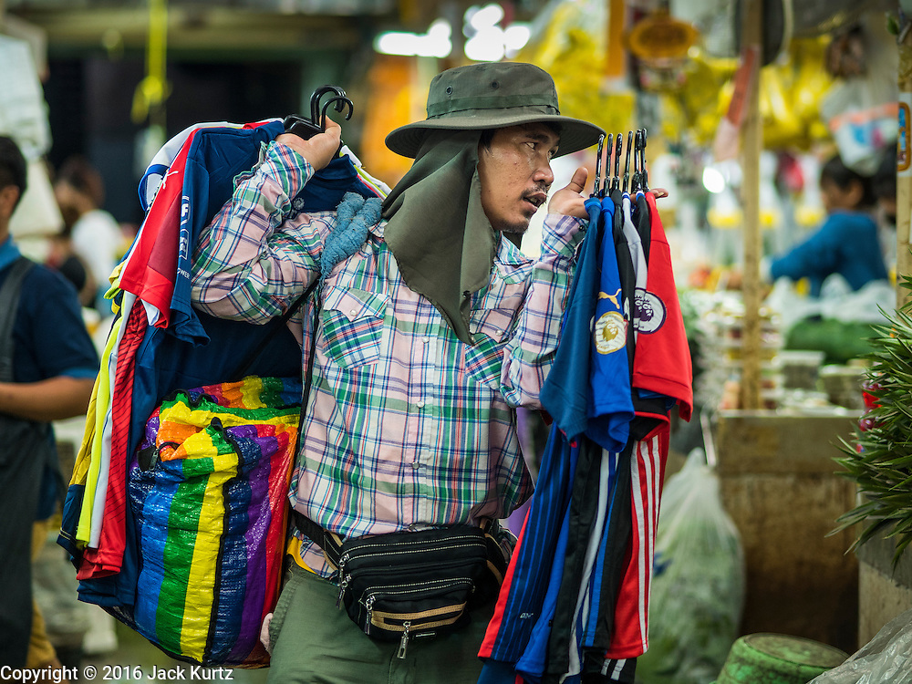 "11 AUGUST 2016 - BANGKOK, THAILAND:  A clothing vendor walks through Pak Khlong Talat selling sports themed jerseys. Pak Khlong Talat (literally ""the market at the mouth of the canal"") is the best known flower market in Thailand. It is the largest flower market in Bangkok. Most of the shop owners in the market sell wholesale to florist shops in Bangkok or to vendors who sell flower garlands, lotus buds and other floral supplies at the entrances to temples throughout Bangkok. There is also a fruit and produce market which specializes in fresh vegetables and fruit on the site. It is one of Bangkok's busiest markets and has become a popular tourist attraction.         PHOTO BY JACK KURTZ"