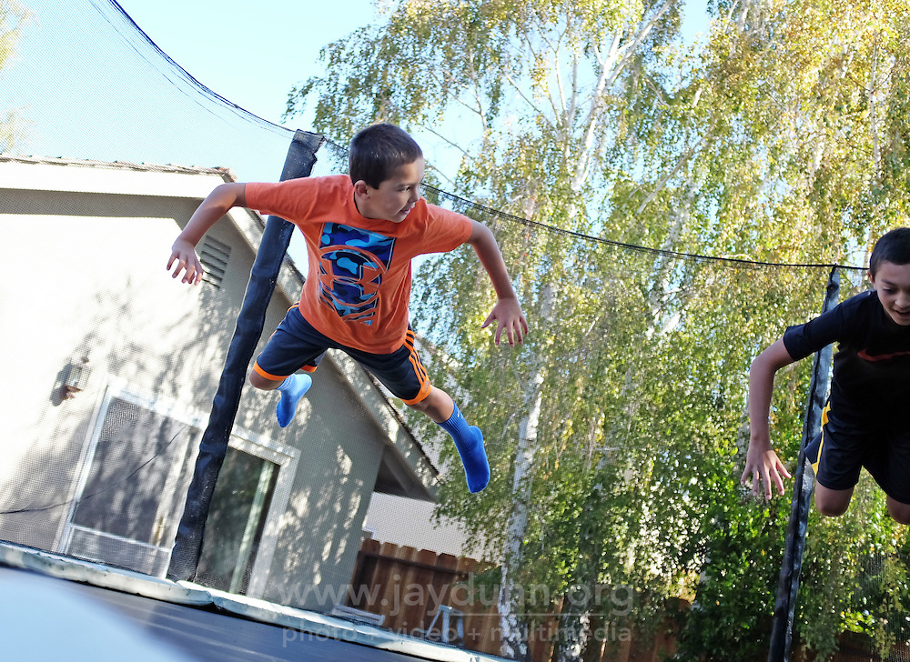 Evan Silacci, left, and his brother Ethan in midair on their backyard trampoline. Evan was diagnosed with MS several years ago.