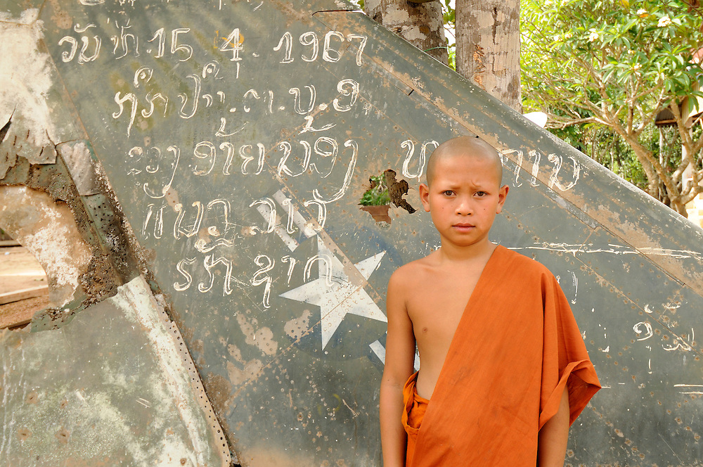 "A novice monk stands outside his temple next to the wing of an American aircraft that was shot down.  Writting on the wing states, ""This plane was shot down by a Vietnamese soldier April 15, 1967...Laos was part of a ""Secret War"", waged within its borders primarily by the USA and North Vietnam.  Many left over weapons supplied by China and Russia continue to kill.  However, between 90 and 270 million fist size cluster bombs were dropped on Laos by the USA, with a failure rate up to 30%.  Millions of live cluster bombs still contaminate large areas of Laos causing death and injury.  The US Military dropped approximately 2 million tons of bombs on Laos making it, per capita, the most heavily bombed country in the world. ..The women of Mines Advisory Group (MAG) work everyday under dangerous conditions removing unexploded ordinance (UXO) from fields and villages...***All photographs of MAG's work must include (either on the photo or right next to it) the credit as follows:  Mine clearance by MAG (Reg. charity)***."