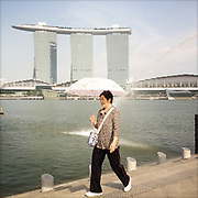 APRIL 15, 2013 — SINGAPORE: A tourist is walking the Merlion Park, a popular landmark and major tourist attraction in Downtown Singapore. The statue spitting water is a mythical symbol. In the background, the Marina Bay Sands Skypark is famous for its architecture and infinity pool at the top.