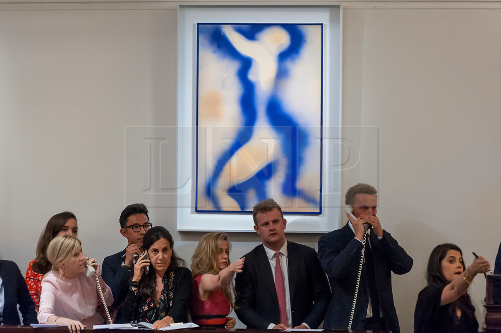 © Licensed to London News Pictures. 26/06/2018. LONDON, UK. Sotheby's staff making bids on behalf of telephone bidders in front of ''Untitled Anthropometry, (Ant 5)'' by Yves Klein, (Est. £5,500,000 - 7,500,000) which sold for a hammer price of £5,800,000 at Sotheby's Contemporary art evening sale in New Bond Street.  Photo credit: Stephen Chung/LNP