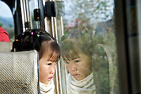 A young girl watches out the window as she rides an outbound bus from Phongsali in northern Laos.