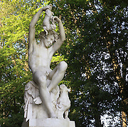 Sculpture of a young poacher in white marble, playfully holding a rabbit above his head and with a dog at his feet, by Charles Gauthier, 1831-91, in the Jardin Anglais or English Garden, laid out in 1812, in the grounds of the Chateau de Fontainebleau, France. The Palace of Fontainebleau is one of the largest French royal palaces and was begun in the early 16th century for Francois I. It was listed as a UNESCO World Heritage Site in 1981. Picture by Manuel Cohen
