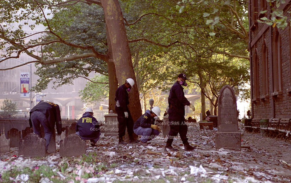 "FBI Agents and other Federal Agents comb the cemetery on their hands and knees searching for evidence from the Sept. 11th attack at the World Trade Center in the cemetery at Trinity Church. Through my eyes and with my camera I am able to see the world we live in, and try to bring things into focus. Photography preserves my vision of what ""I see"" at a specific time and place- a moment. Creating a bond between  me and my subject and capturing and emotion for eternity. Having lived and worked in New York City for over 15 years when 911 happened. I had to go and ""see"" with my camera what lower Manhattan was like after this horrific attack on our Nation. The World Trade Center owned the skyline in lower Manhattan making it feel more like a canyon. After the Twin Towers fell, and I saw with my own eyes and camera the destruction, I realized what little land they actually sat on. The Twin Towers may not have occupied a large plot of land but they now touched everyones life. Photo©SuziAltman"