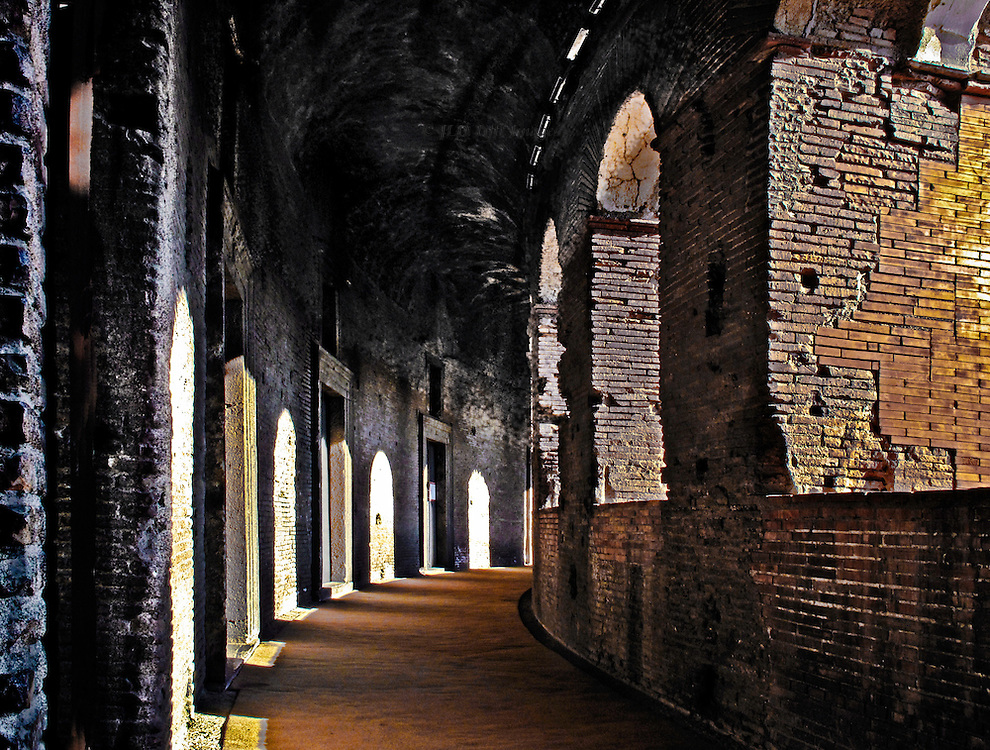 Interior corridor of the hemicycle in Trajan's Markets, Rome.  Sunlight streams through arched openings on the right to fall on shop entrances on the left.