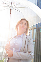 Low angle view of thoughtful businesswoman holding umbrella outdoors