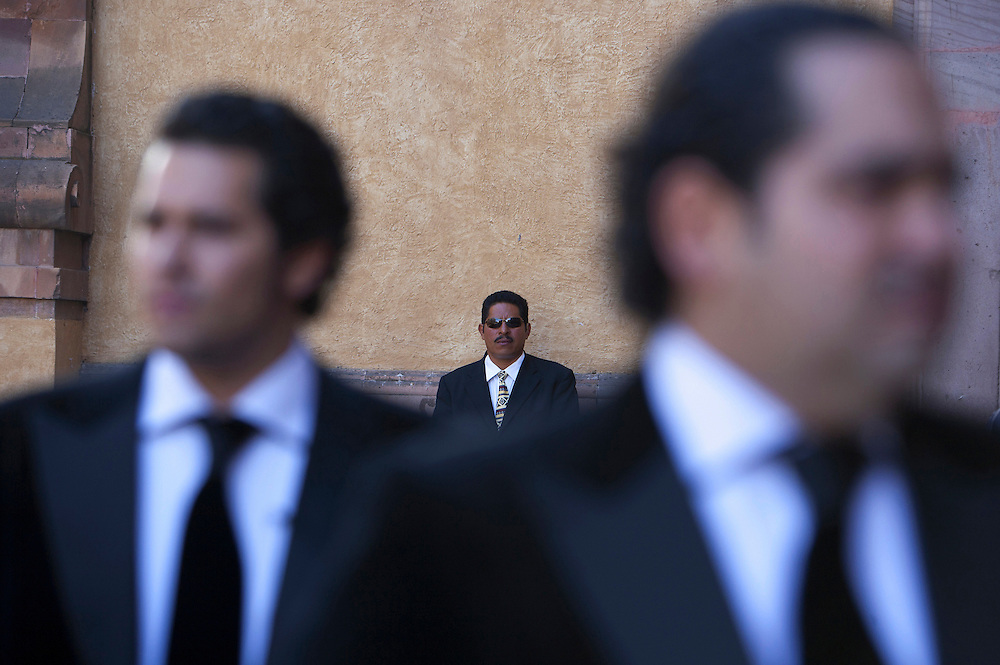 José and his brother greet guests outside a Mexican cathedral before the advent of the brother's wedding, while being carefully watched over by a member of their professional security team. As a result of Mexico's increasing violence, many of the country's elites are taking protection into their own hands, by hiring private security bodyguards.